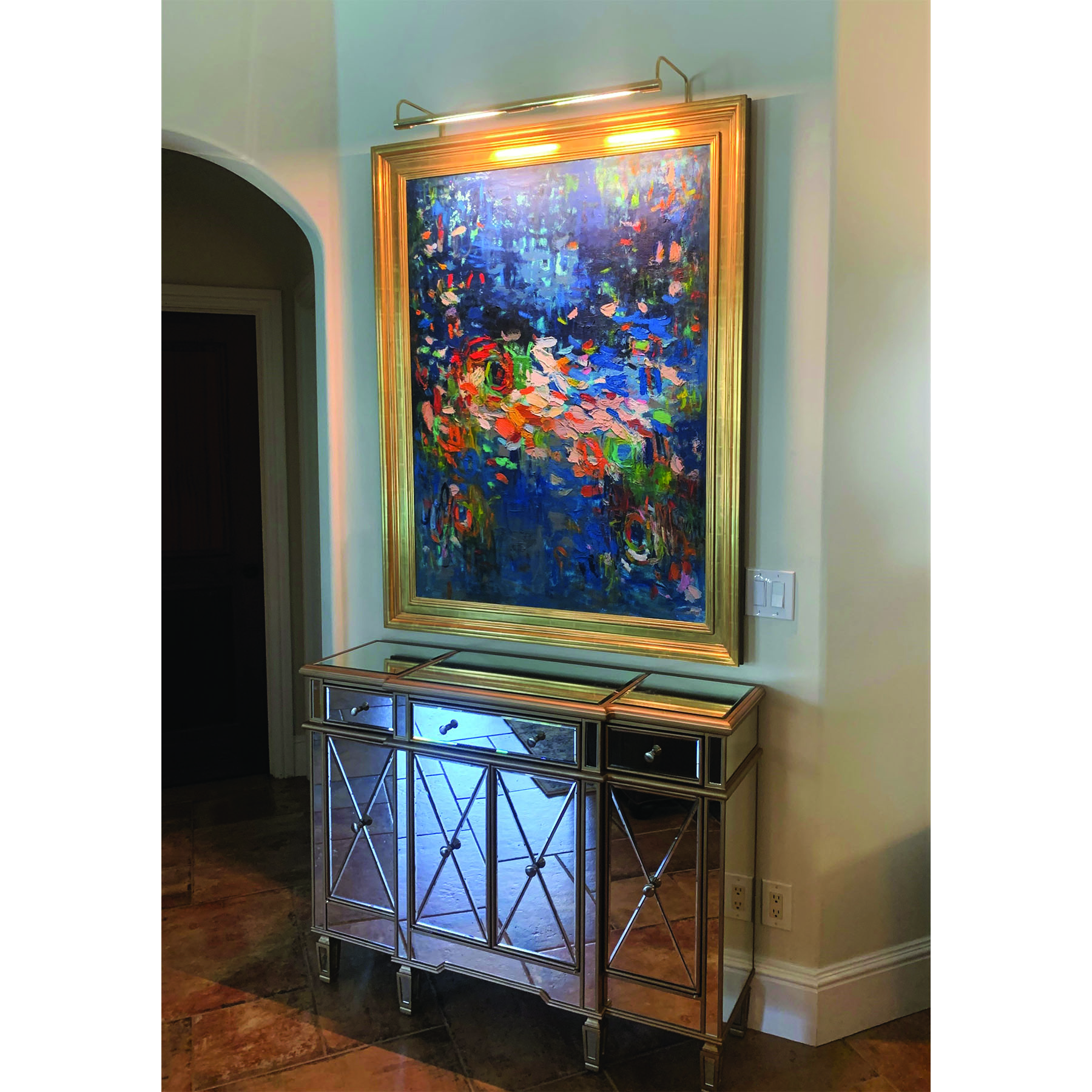 Abstract painting with gold frame installed in a home