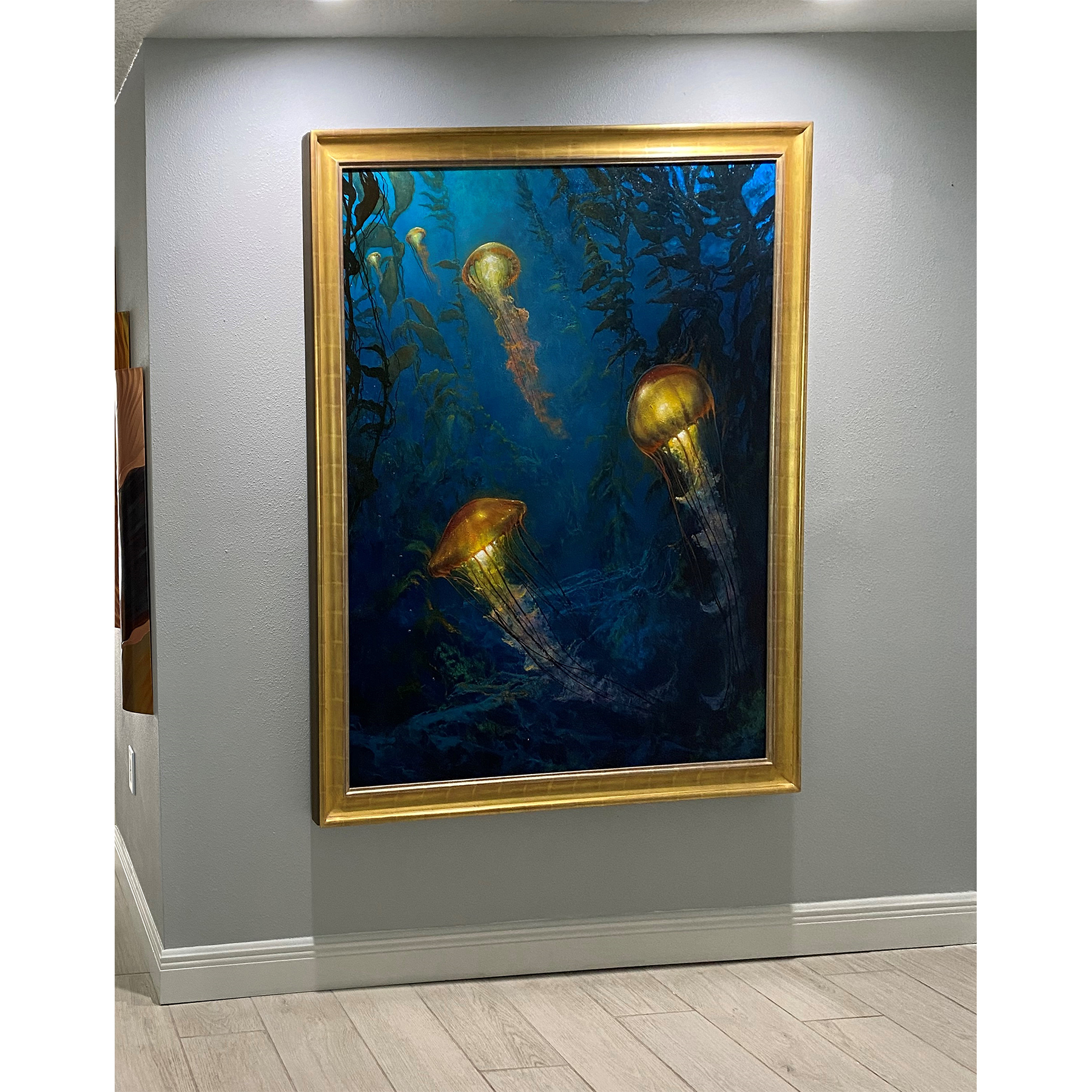 Gold-framed painting of jellyfish installed in a home