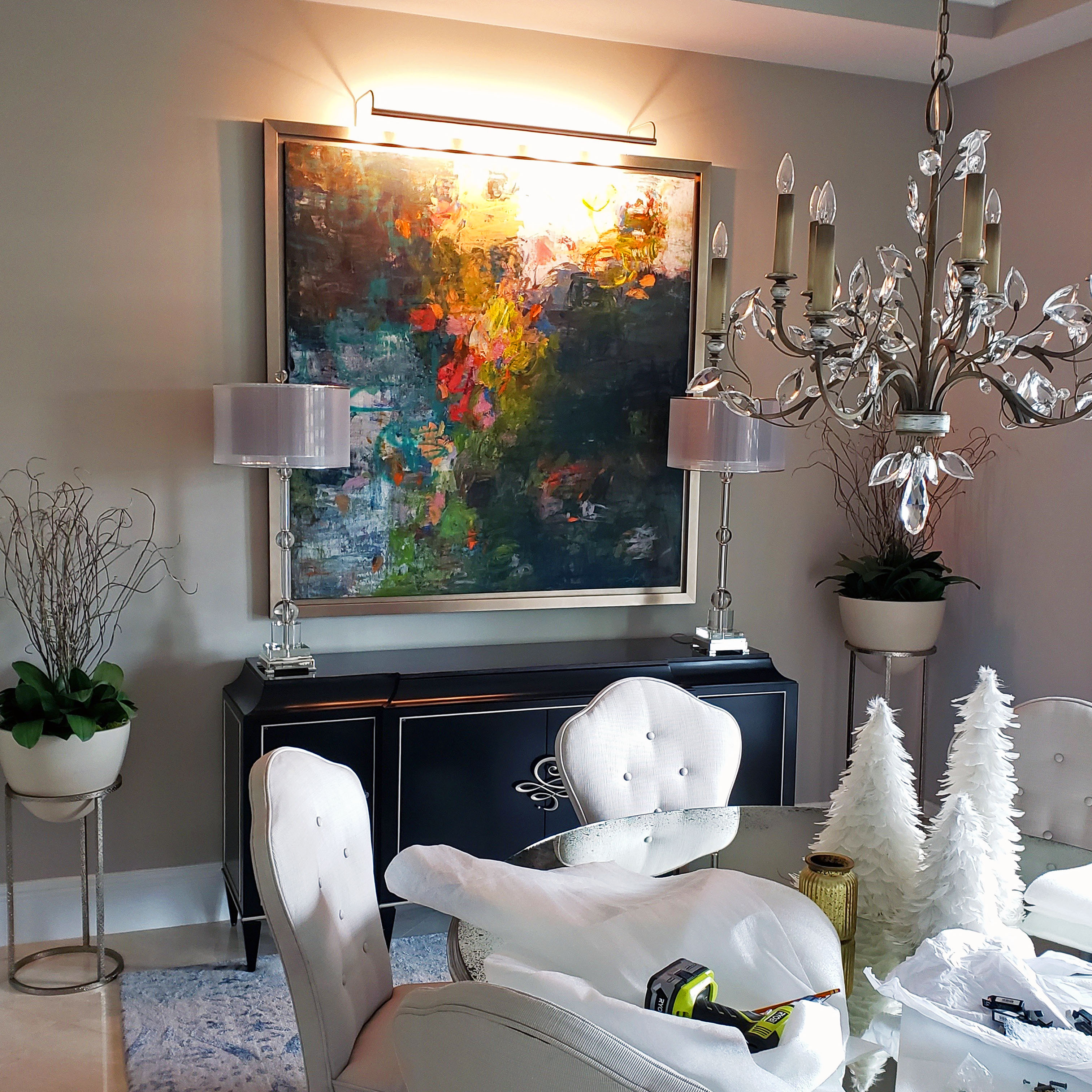 Abstract painting in a silver frame installed in a dining room