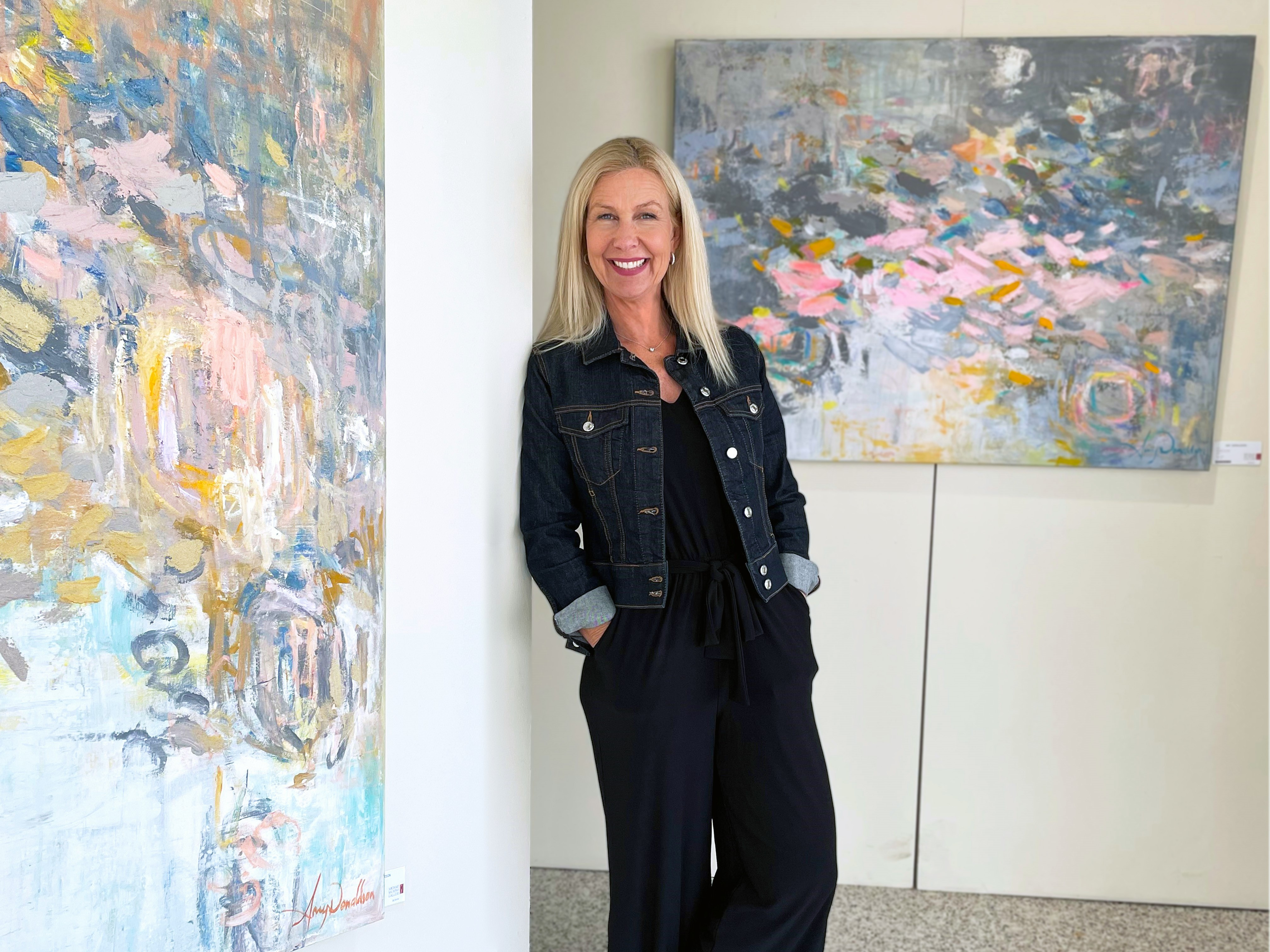 Gallery director Deana Buckley with abstract paintings