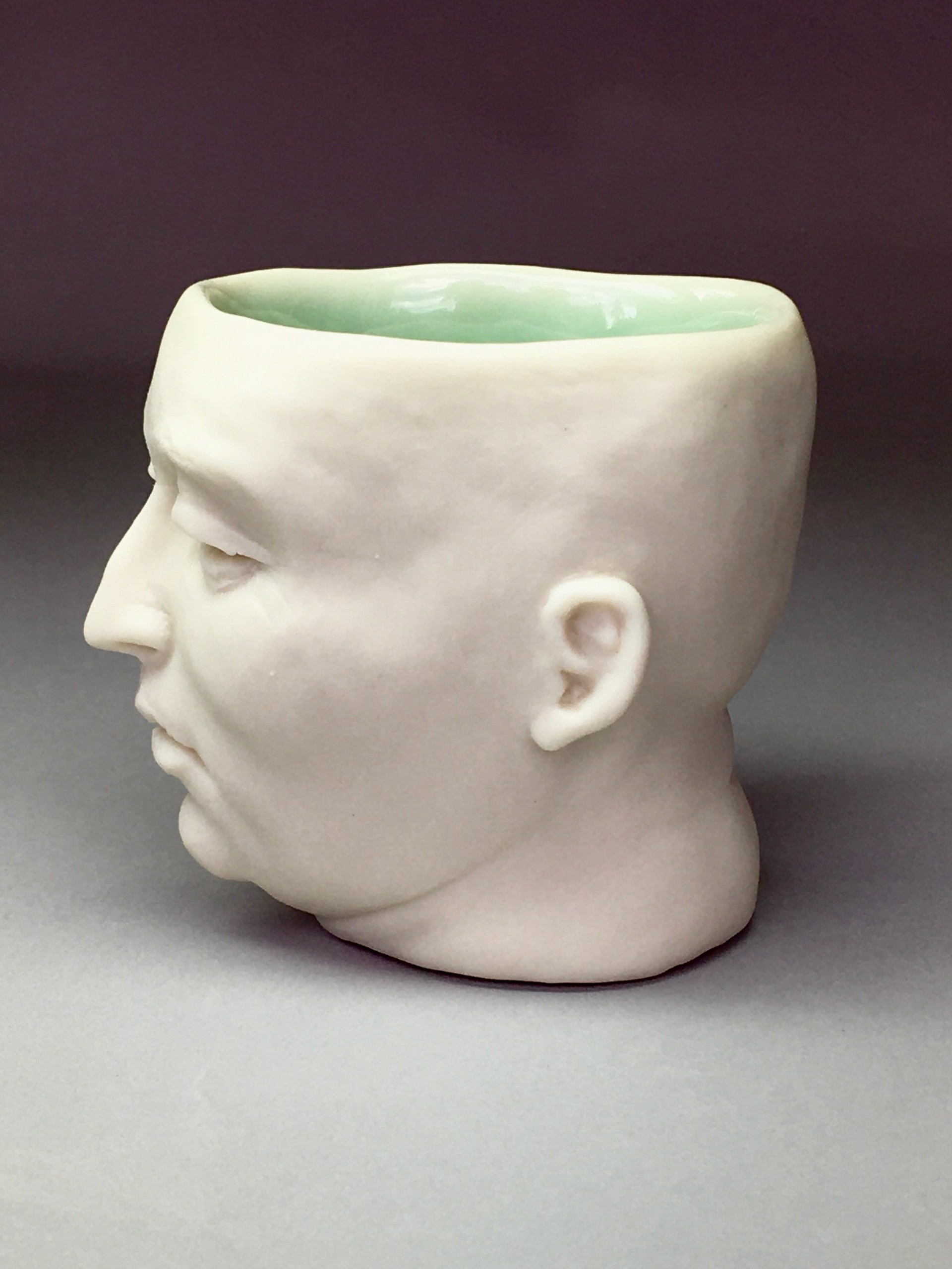 """""""Somewhat Pissed-off Friend Shot Glass"""" (light green interior, eyes open) by Adrian Arleo"""