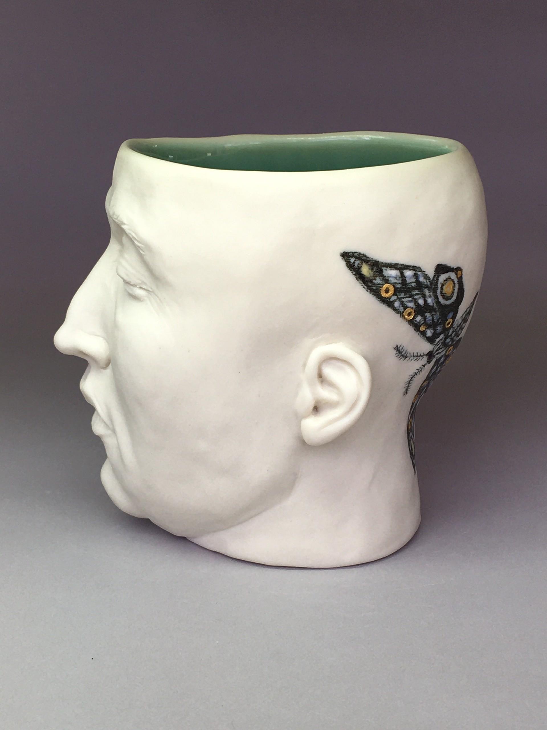 "Moth Cup III"" (left side, deep green celadon, eyes closed) by Adrian Arleo"
