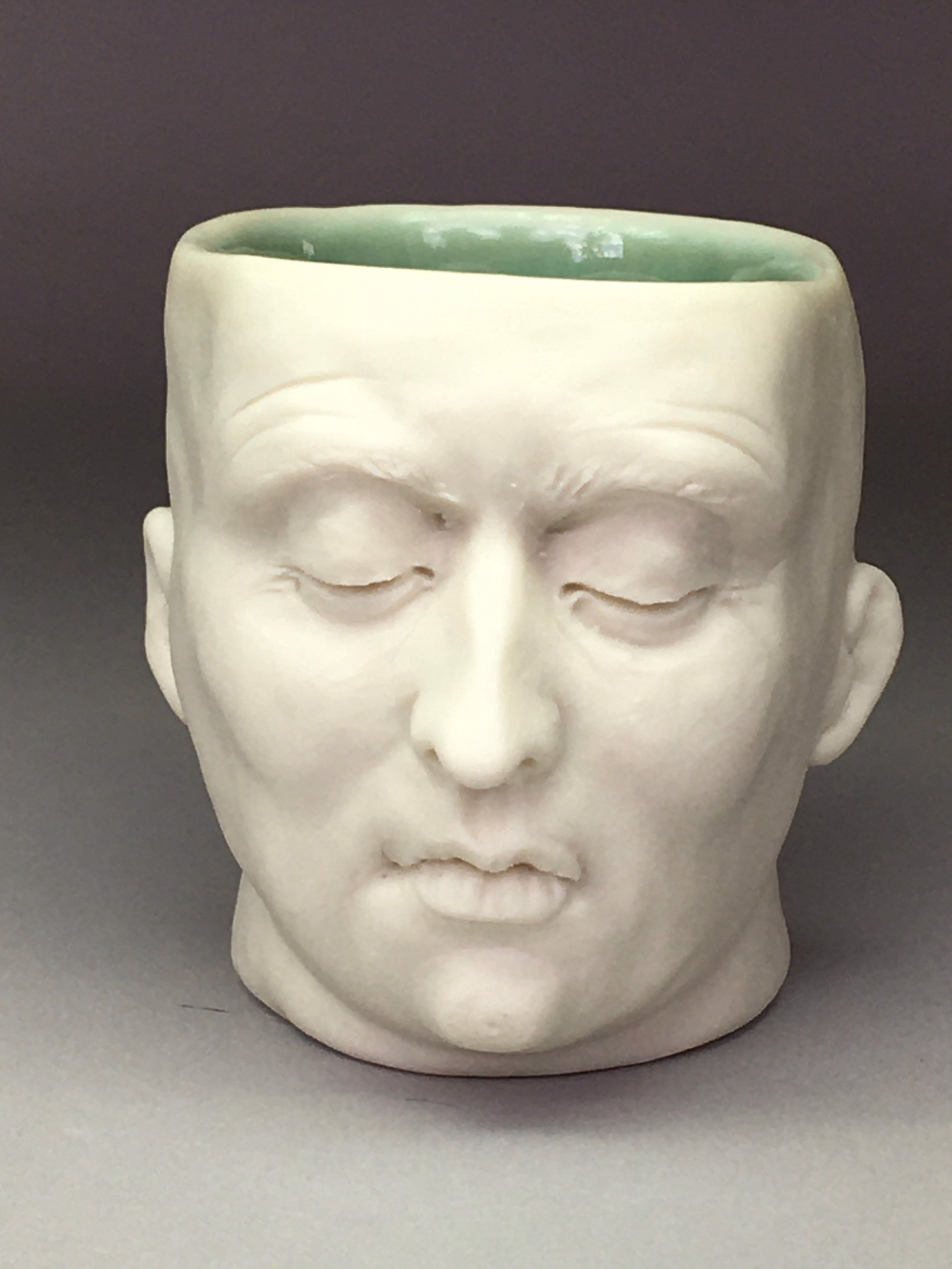 """Concerned Friend Shot Glass I"" (dark green interior, closed eyes) by Adrian Arleo"
