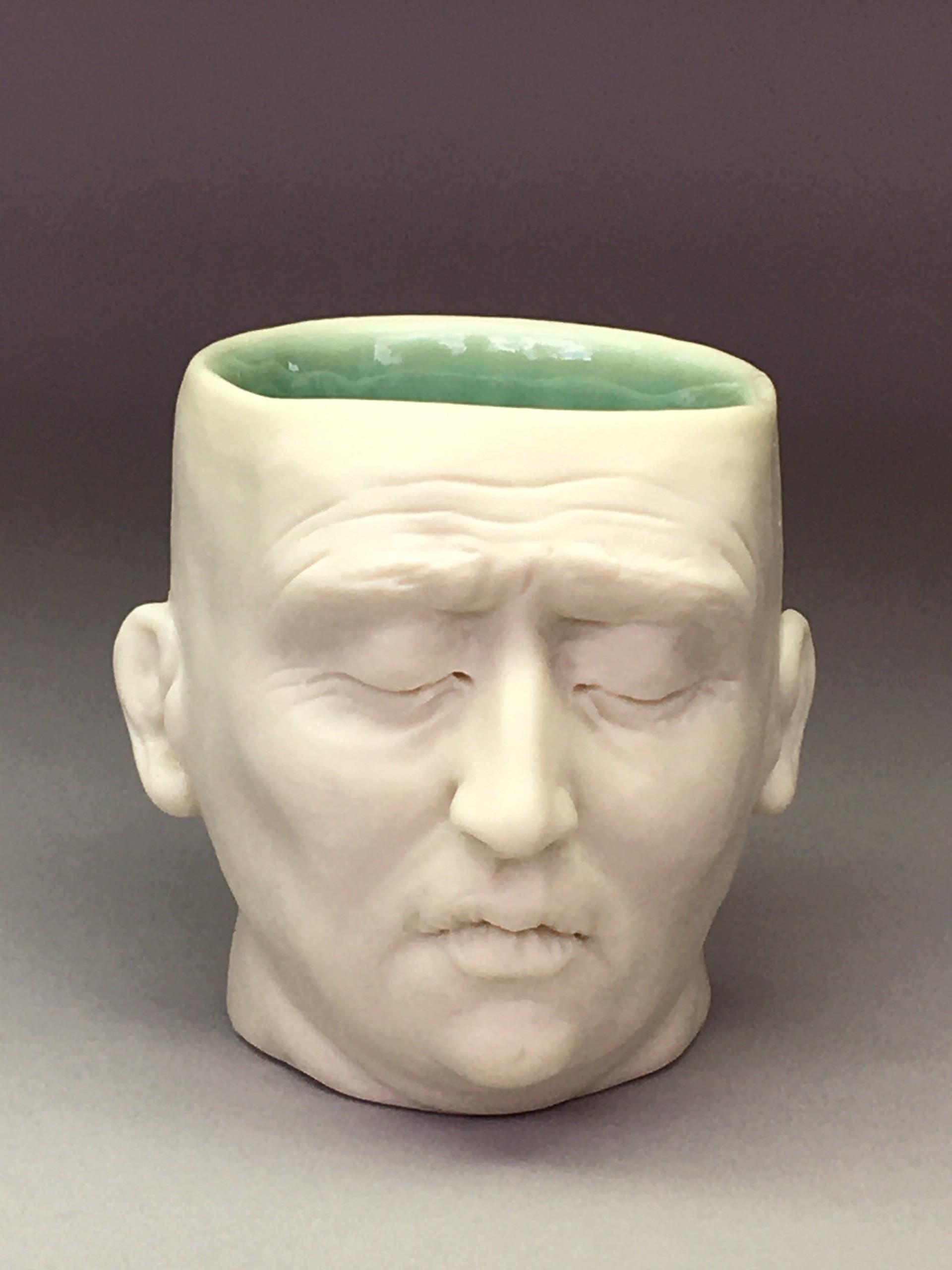 """Worried Friend Shot Glass II"" (dark green interior, closed eyes) by Adrian Arleo"