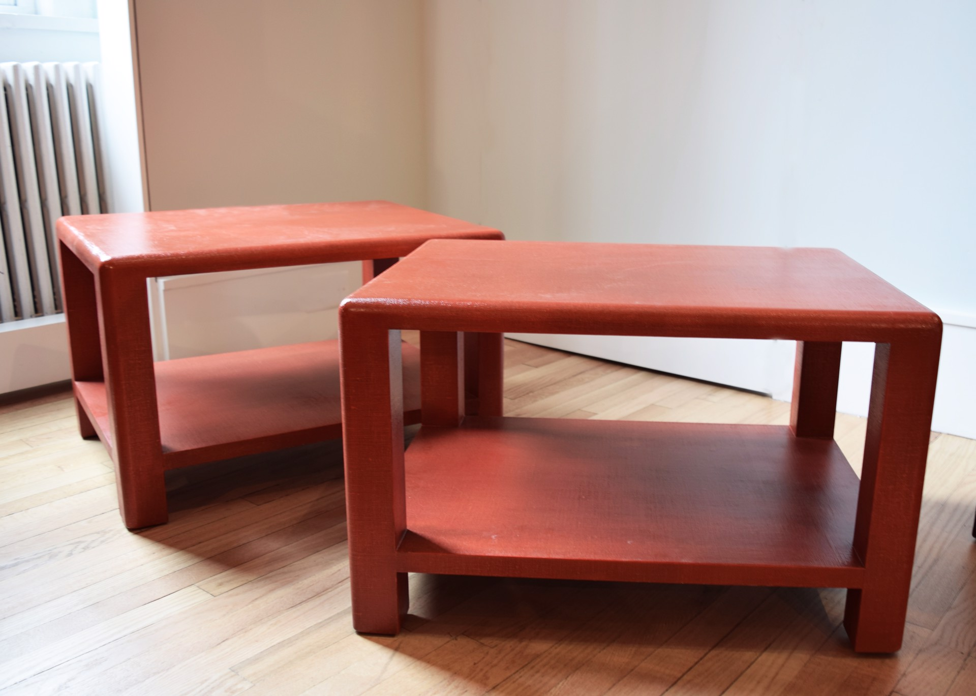 PAIR OF RED LACQUERED LINEN SIDE TABLES by Ron Seff