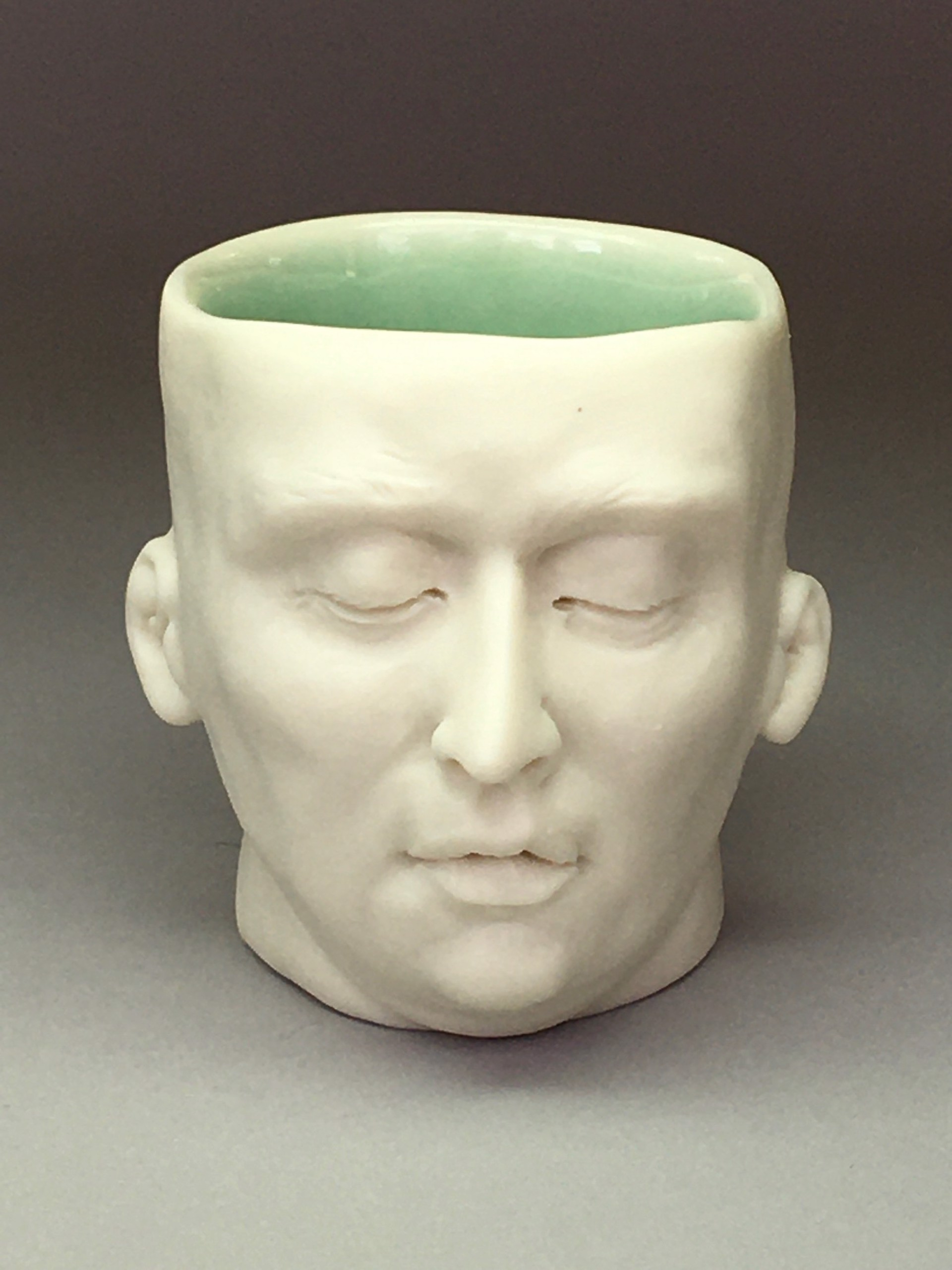 """""""Tranquil Friend Shot Glass"""" (light green interior, closed eyes) by Adrian Arleo"""