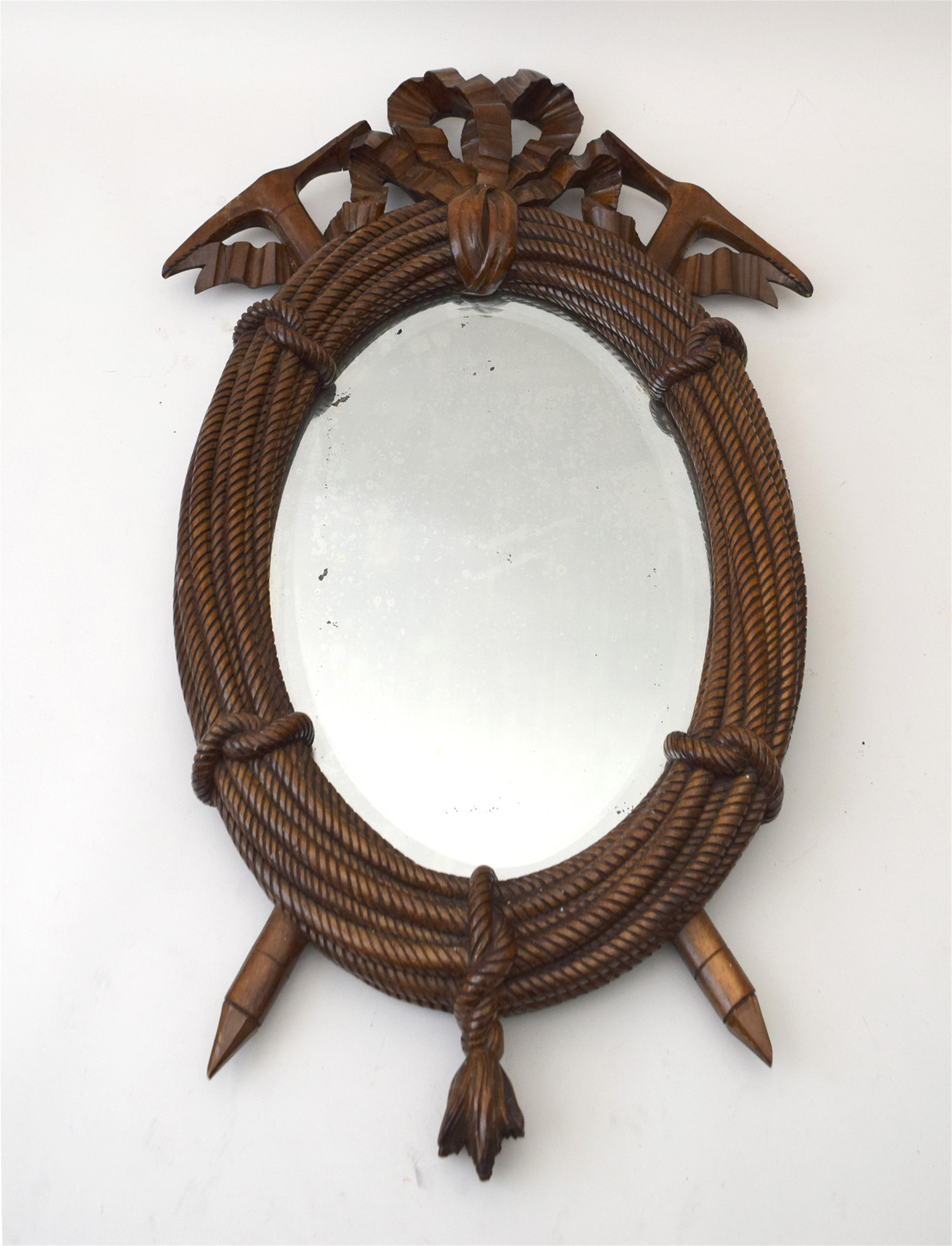 SMALL OVAL MIRROR CARVED WITH BOW-TIED COILED ROPE AND CROSSED PICK AXES