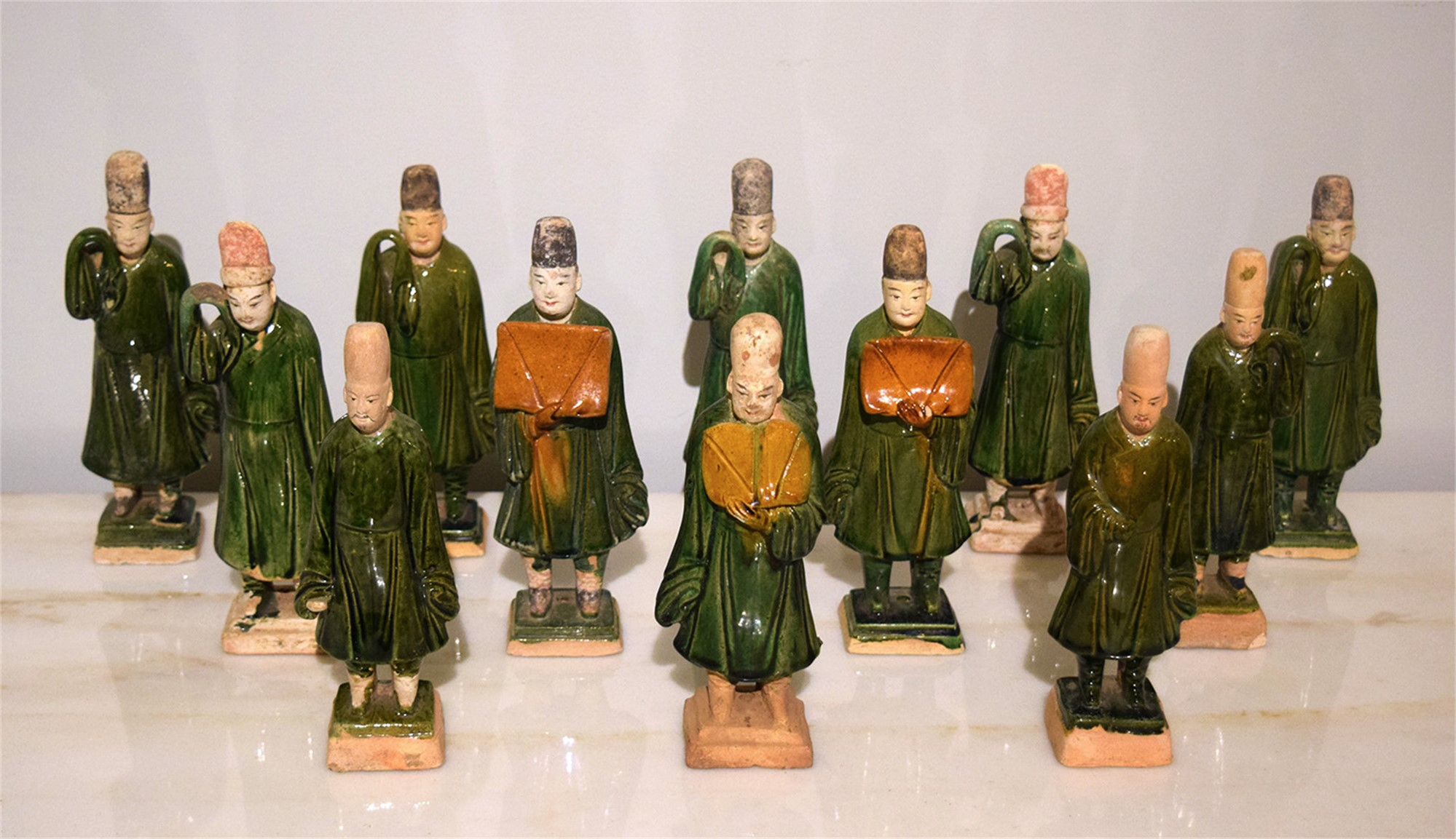 SET OF 12 GREEN-GLAZED POTTERY ATTENDANTS