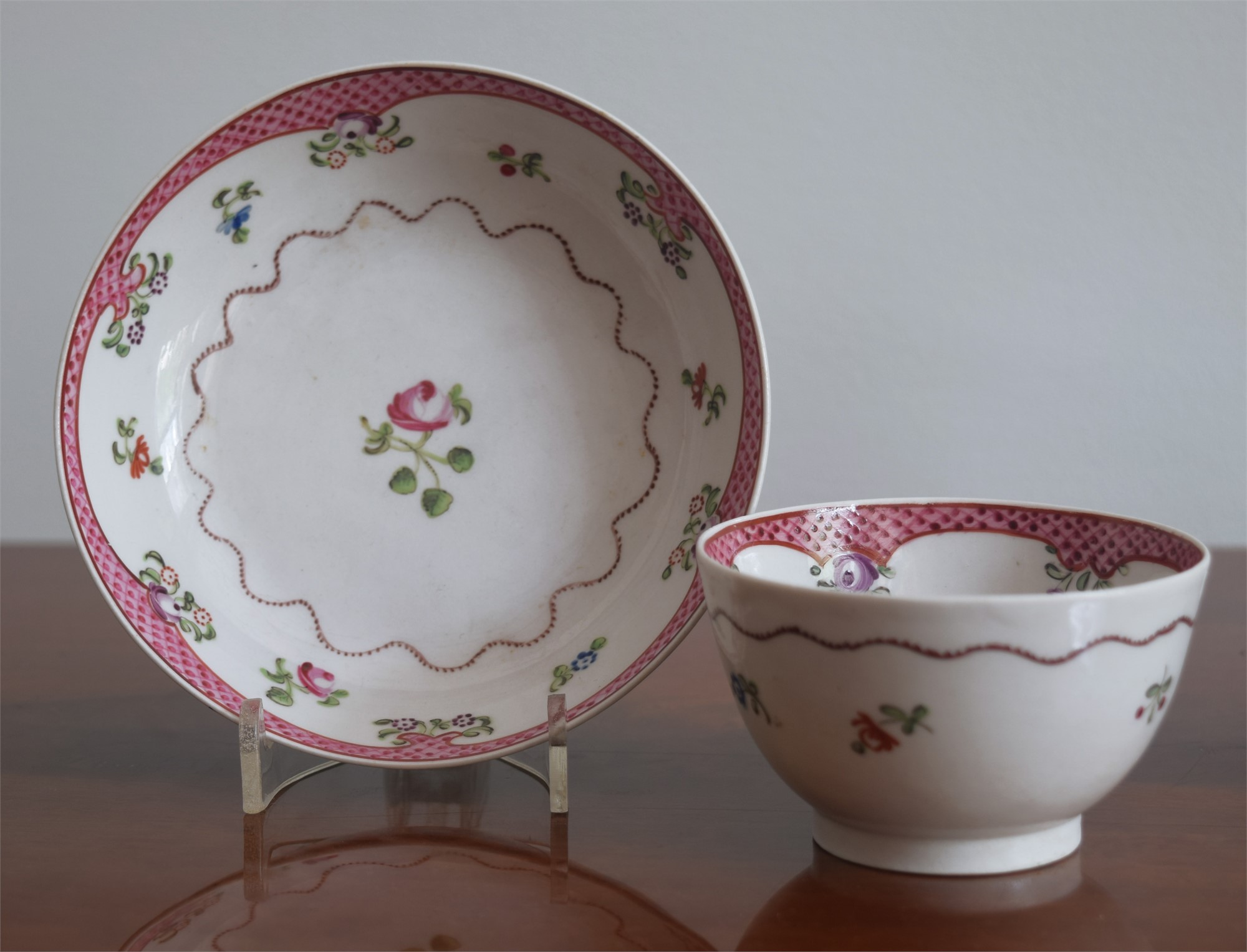A FAMILLE-ROSE TEACUP AND SAUCER WITH LATTICE RIMS