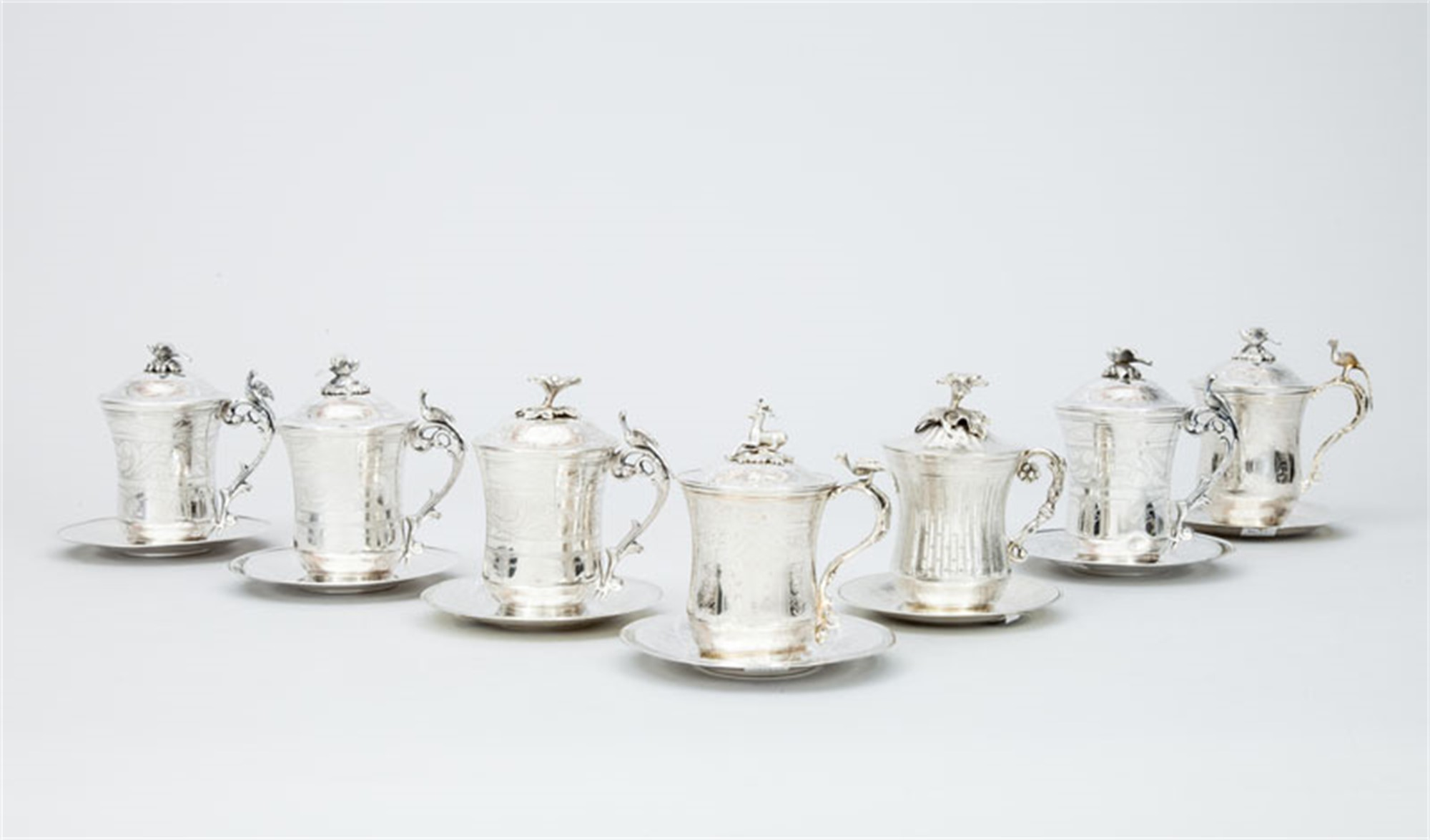 GROUP OF SEVEN STERLING SILVER TANKARDS WITH LIDS AND SAUCERS