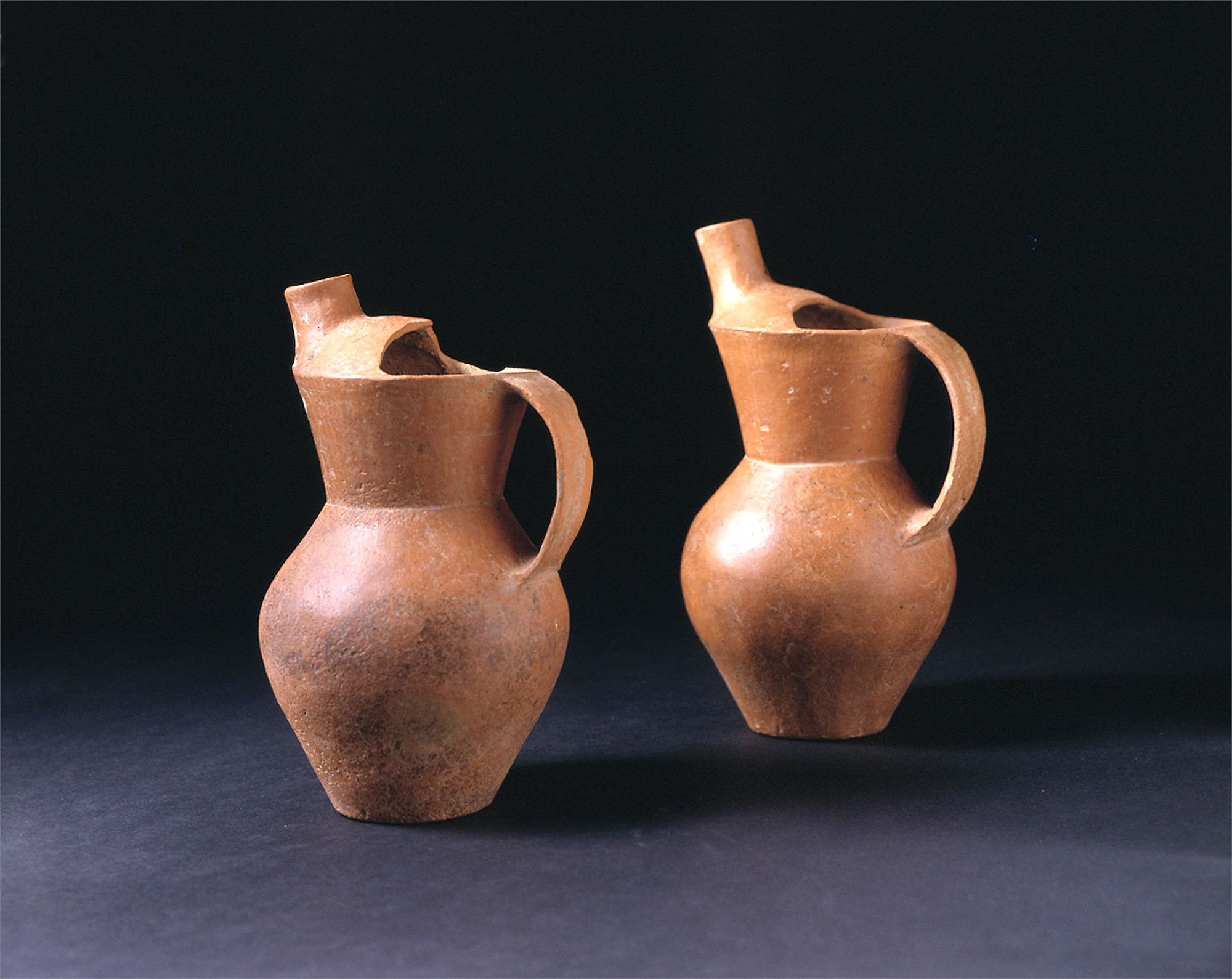 PAIR OF RED POTTERY EWERS
