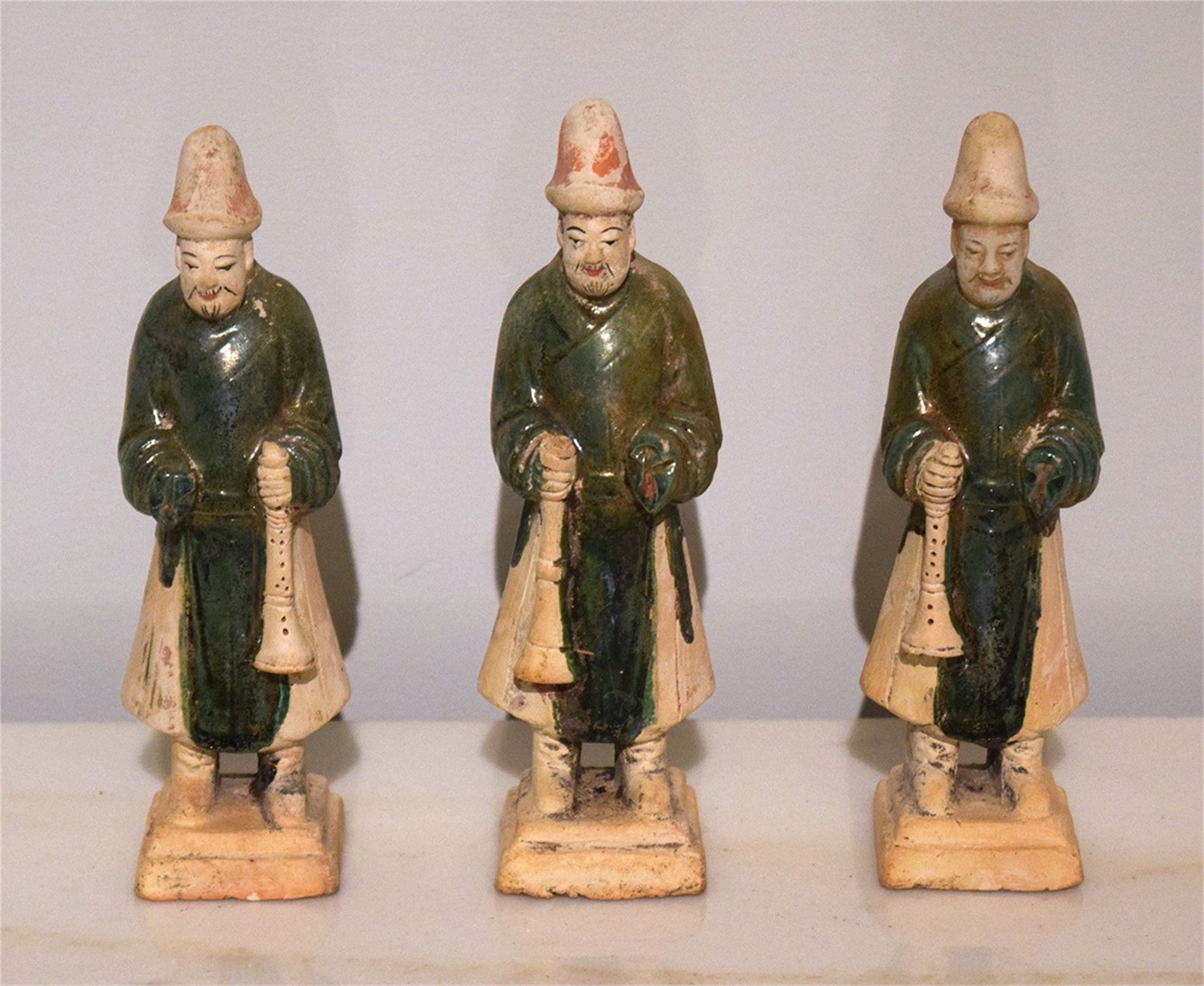 SET OF 3 GREEN-GLAZED POTTERY TRUMPETERS