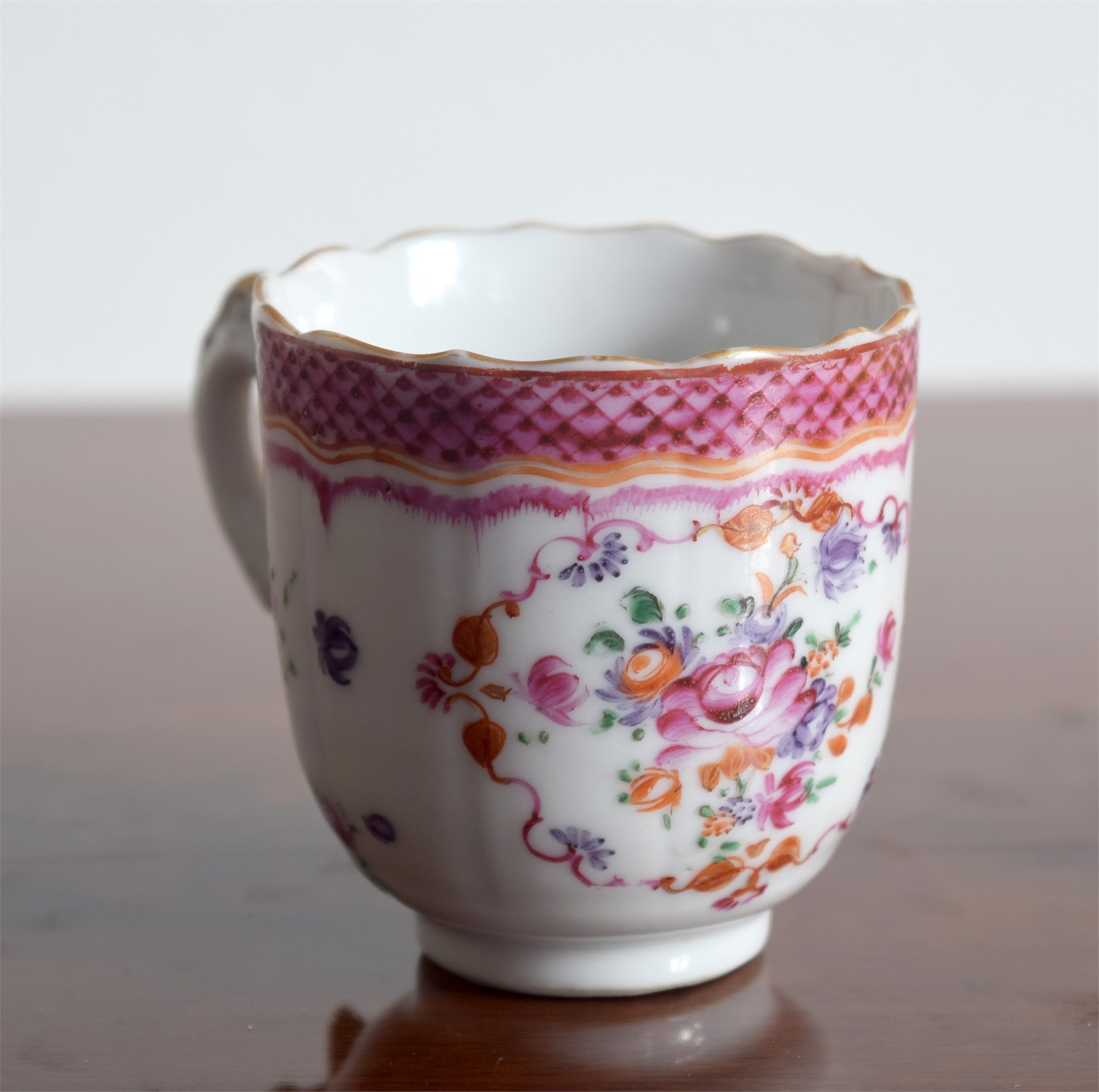 A FR COFFEECUP WITH CENTRAL FLOWER, SMALL PUCE FOLIAGE, BARBED RIM