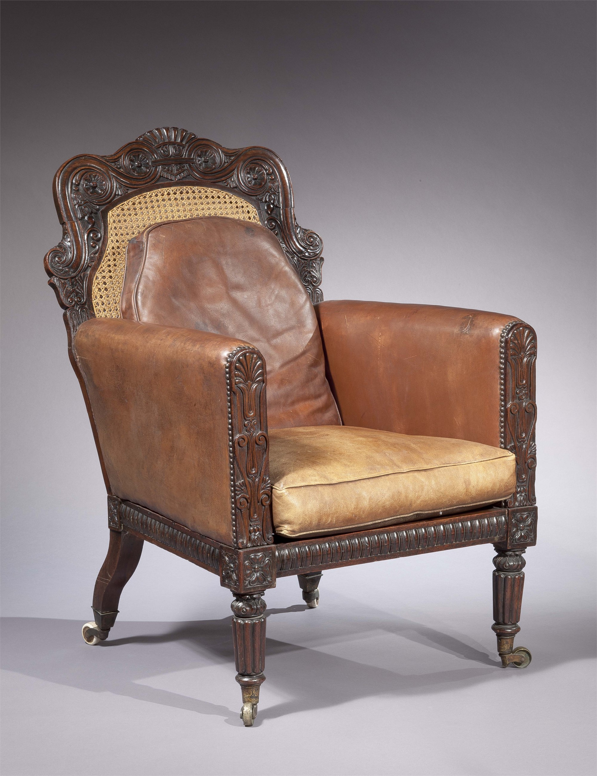 ANGLO-INDIAN ROSEWOOD, CANED, LEATHER-UPHOLSTERED ARMCHAIR