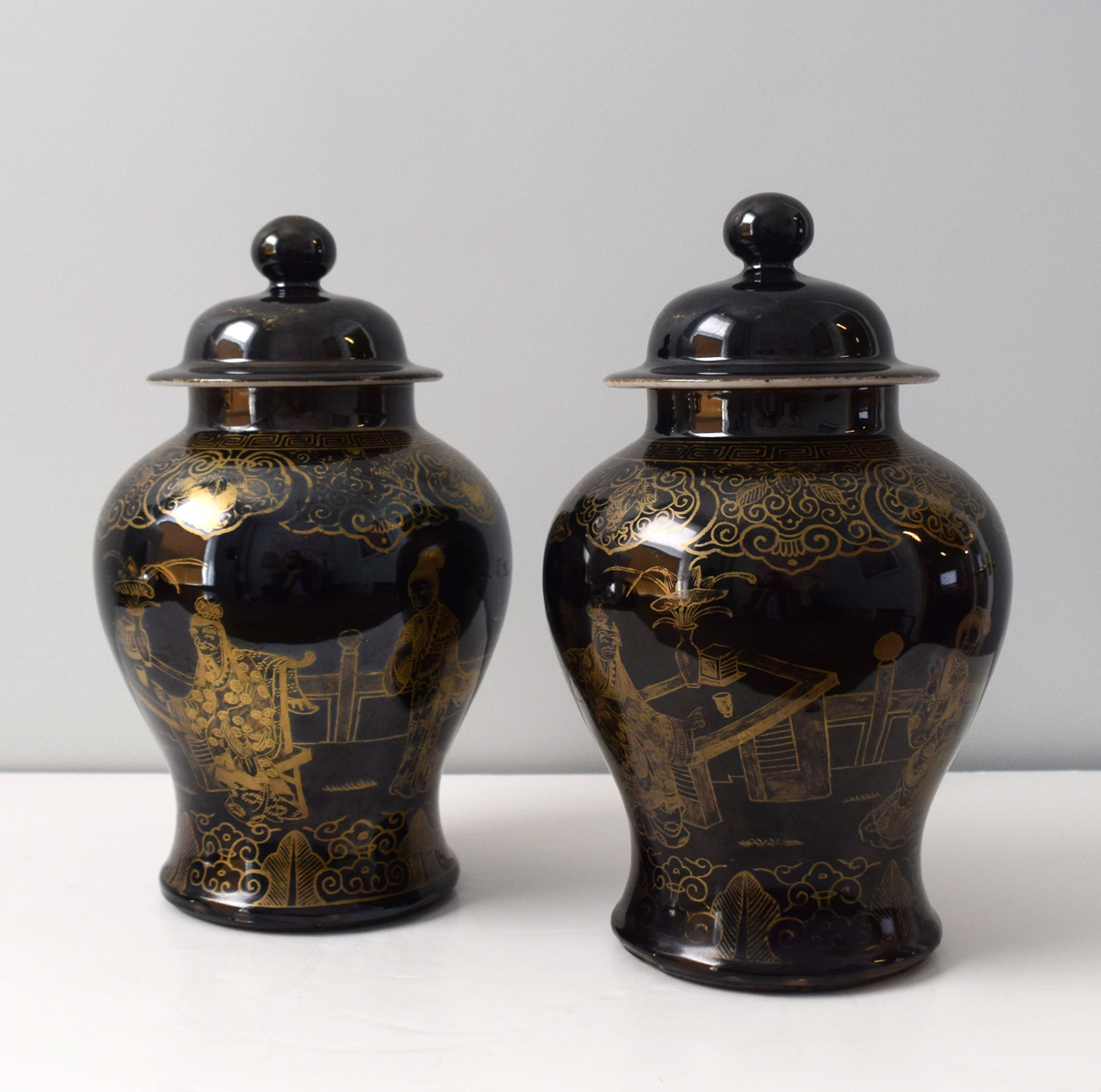 PAIR OF BLACK GROUND AND GILT BALUSTER JARS AND COVERS WITH FIGURES