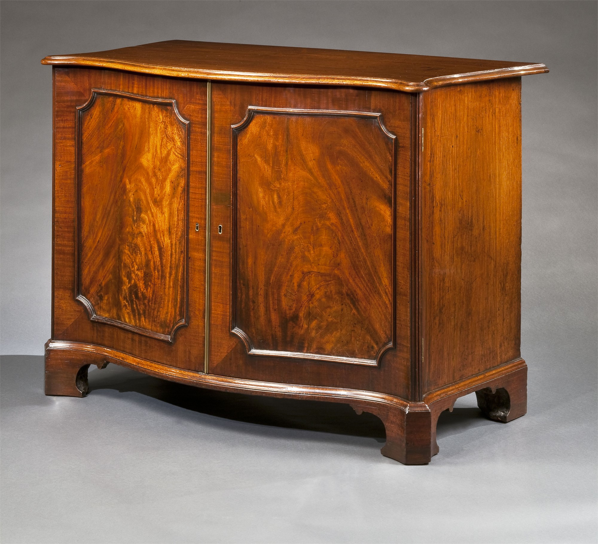 GEORGE III MAHOGANY SERPENTINE COMMODE by Thomas Chippendale