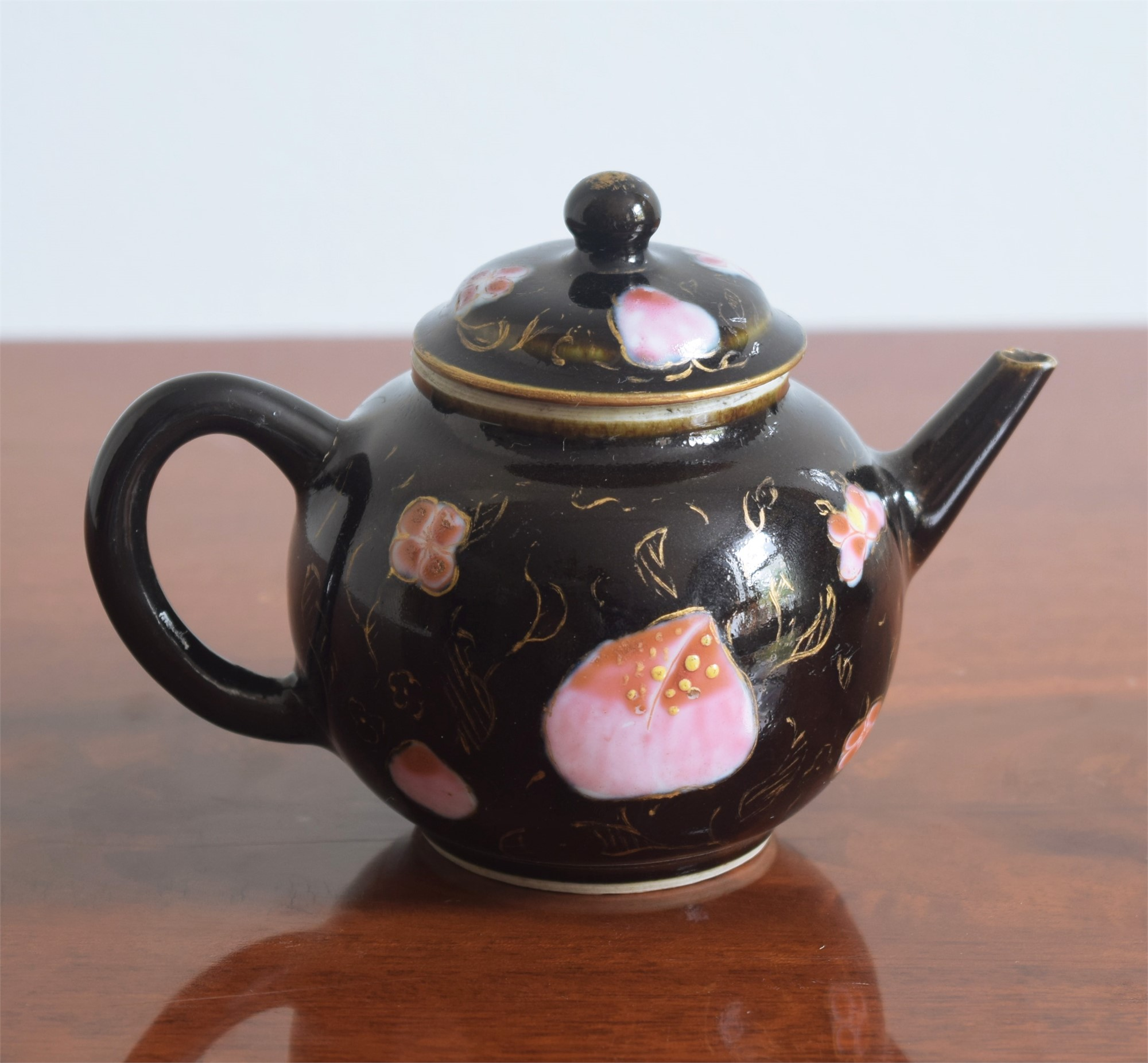 A BLACK GROUND TEAPOT AND COVER WITH FAMILLE-ROSE BLOOM