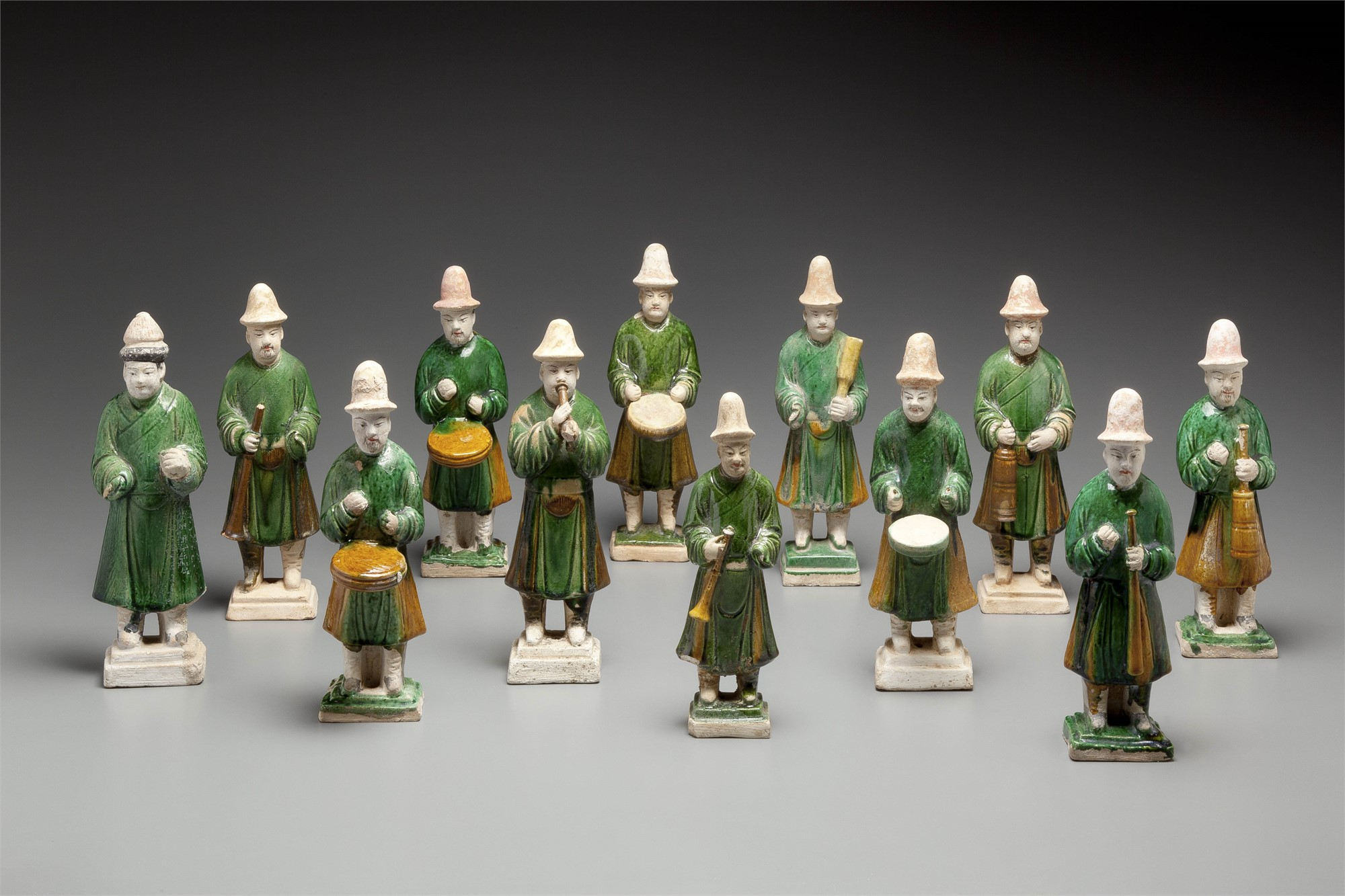 SET OF 12 GREEN-GLAZED POTTERY MUSICIANS