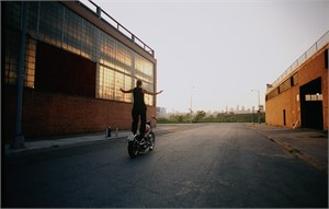 03050 Indian Larry Standing on Bike From Behind Color, 2003