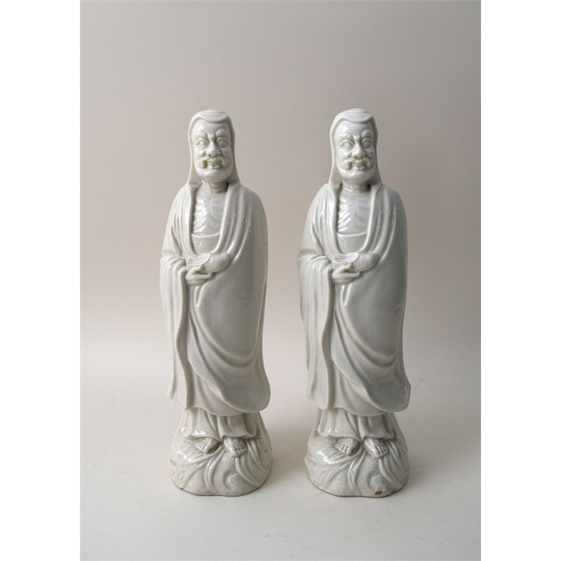 PAIR OF BLANC-DE-CHINE FIGURES OF DAMO HOLDING A SHOE ON WAVE BASE, Kangxi Period, circa 1690